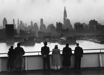 Passengers on board the Cunard White Star liner Queen Mary view the New York skyline as the ship docks in Manhattan at dawn, 1939.